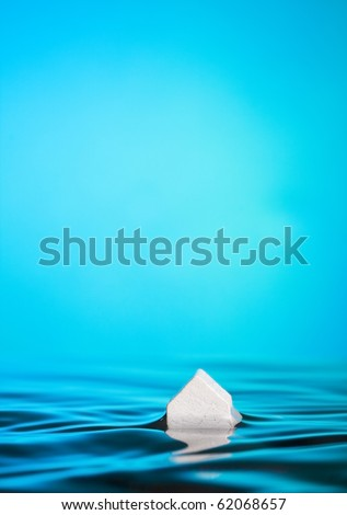 Flood or foreclosure Concept. Abstract Macro of a little white house in water against blue with ample space for copy. - stock photo