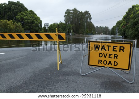 Flooded australian road with road block - stock photo