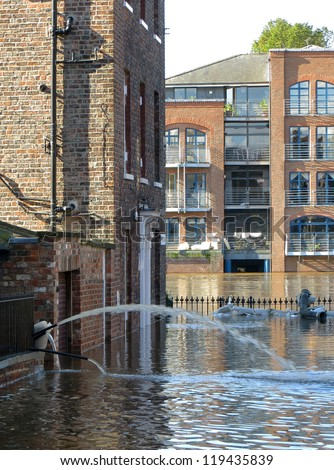 Flooded city steet leading to swollen River Ouse. York, North Yorkshire, UK. - stock photo