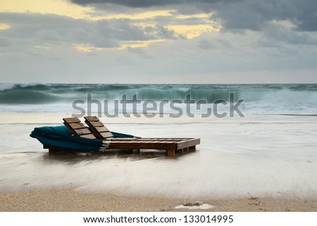 Flooded Florida Beach at High Tide,  Surf Sweeping Beach Chairs at Sunrise - stock photo