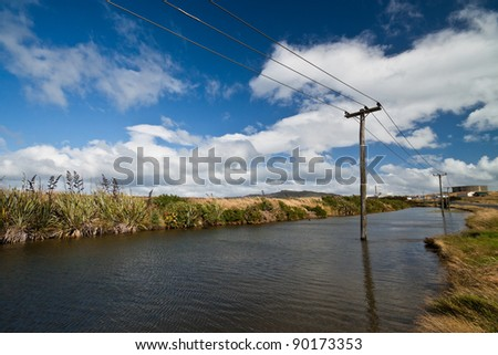 Flooded old wooden electricity pylons. - stock photo
