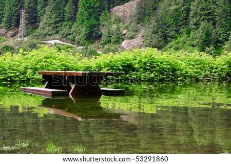 Flooded picnic table and beach. Climate change concept. - stock photo