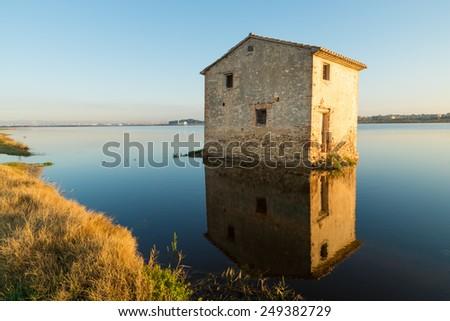 Flooded rice paddy and traditional Mediterranean farm house, Albufera scenics, Valencia, Spain - stock photo