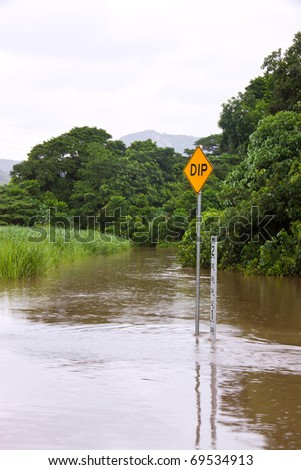 Flooded road with depth indicators and dip sign in Queensland, Australia - stock photo