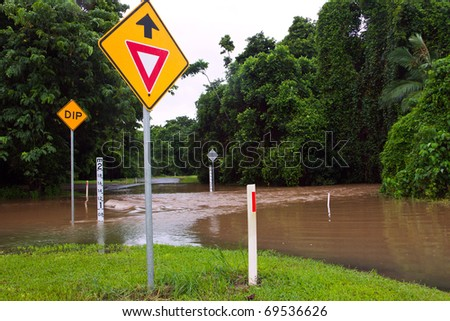 Flooded road with depth indicators and give way and dip road signs  after heavy rain and flooding in Queensland, Australia - stock photo