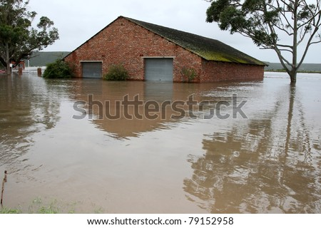 Flooded store room building with water half way up it's walls - stock photo