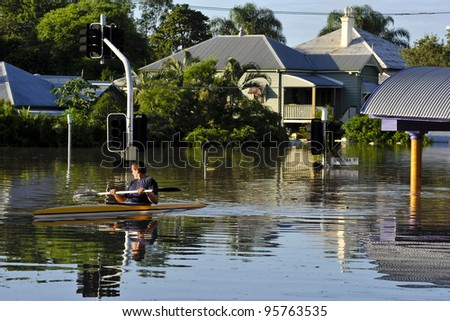 flooded streets: a man uses a canoe to traverse the flooded streets of his suburb. Rosalie, Brisbane, 2011 - stock photo