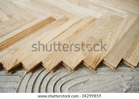 Floor construction, installing wood parquet pieces - stock photo