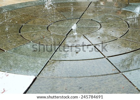 Floor fountain splashing water jets upwards into the air - stock photo