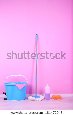 Floor mop and bucket for washing in room on pink wall background - stock photo