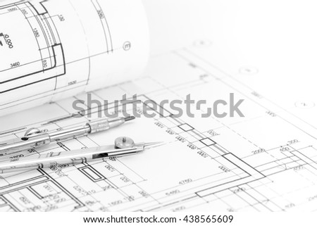 floor plan with rolled blueprint and drawing compass - stock photo