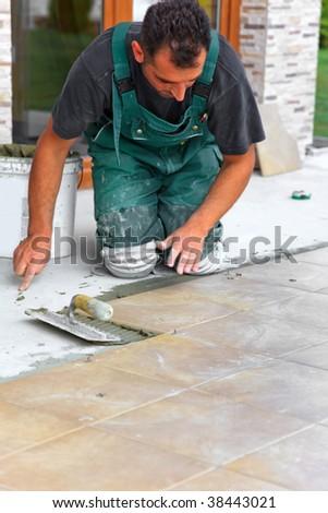 Floor tiles installation. Man installs ceramic tile - stock photo