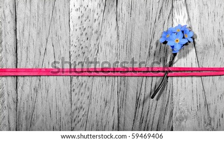 """Floral arrangement of a """"forget me not""""-flower fixed with a red ribbon band on a wooden background - stock photo"""