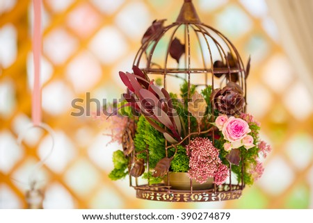 floral arrangement of flowers, bird cage with flowers - stock photo