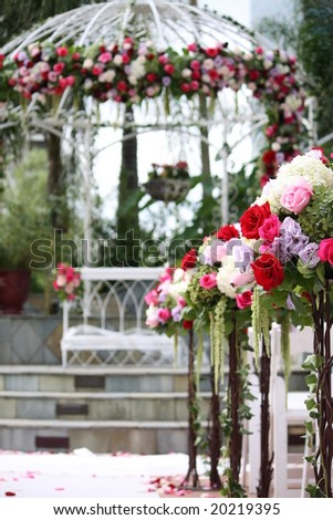 Floral Arrangement on Wedding Aisle with Gazebo in Background - stock photo