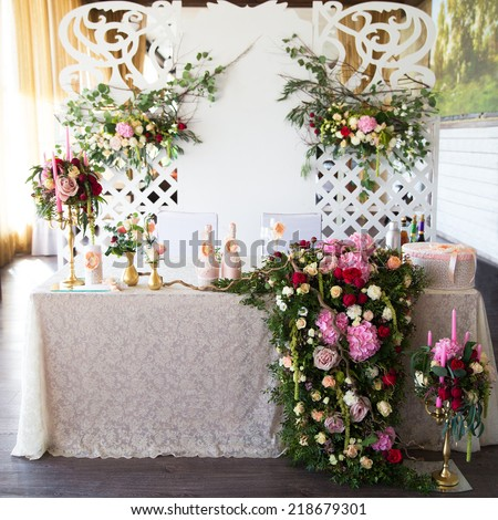 Floral arrangement to decorate the wedding feast, the bride and groom. Flowers, candles, a bottle of champagne. The vintage. - stock photo