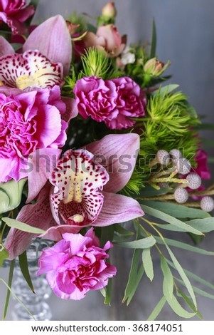 Floral arrangement with orchids, carnations and brunia flowers - stock photo