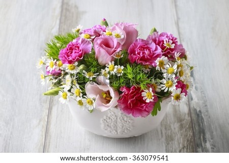 Floral arrangement with pink eustomas, carnations and chamomile flowers
