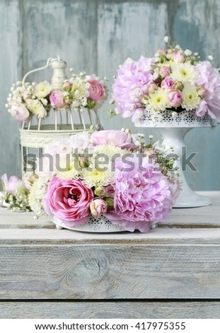 Floral arrangement with pink peonies, tiny roses, chrysanthemums and gypsophila paniculata twigs - stock photo