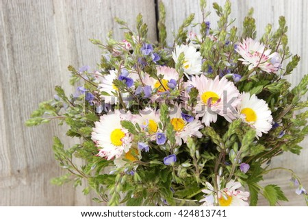 Floral background with bouquet of blue wildflowers, grass and pink daisies. Concept for greeting card: birthday or valentine theme