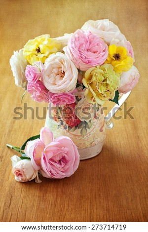 Floral composition with a roses in a vintage jug on a table. vintage style ,grunge paper background.  - stock photo