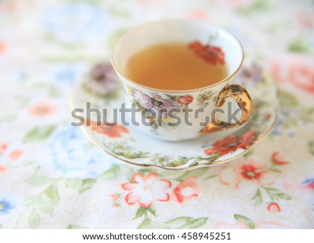 Floral cup with tea on a flowery cloth - stock photo