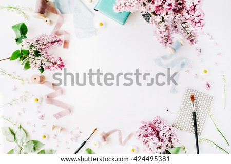 floral frame with lilac flower, chamomile, fresh branches and spool with blue and beige ribbon, notebook isolated on white background. flat lay, top view