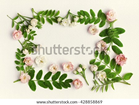 Floral framed background. Green plant leaves, little delicate flowers on paper backdrop.  Spring blossom pattern. - stock photo