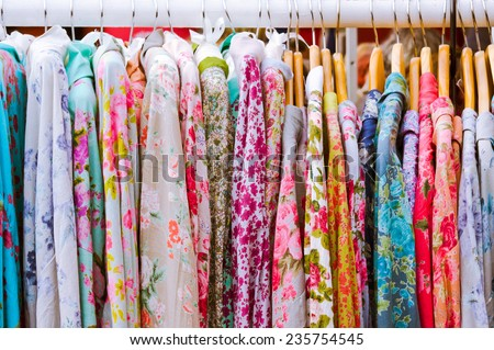 Floral patterned vintage dresses at a market - stock photo