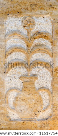 Floral stone decorative panel on a wall depicting a flowering plant in a two handled amphora - stock photo