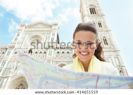 Florence invite you. Smiling woman near Cattedrale di Santa Maria del Fiore looking at the map - stock photo