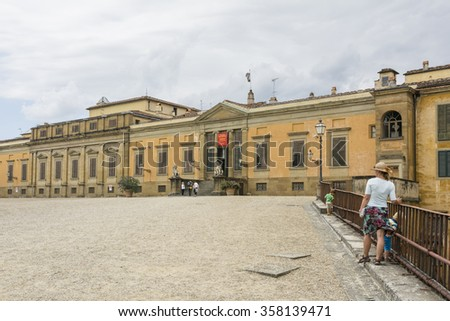 FLORENCE,ITALY-AUGUST 26,2014:A woman and her two children strolling in the Boboli gardens and admire the famous palace during a cloudy day.