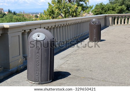 Florence, Italy - August 19, 2015: Two cylindrical trash containers with ashtray and logo QUADRIFOGLIO on a street in Florence, Italy - stock photo