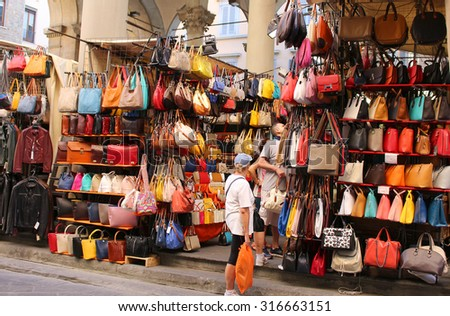 FLORENCE, ITALY, JUNE 23, 2015 : An outdoor market selling colorful leather goods such as handbags and jackets in the centre of the city in Florence Italy - stock photo