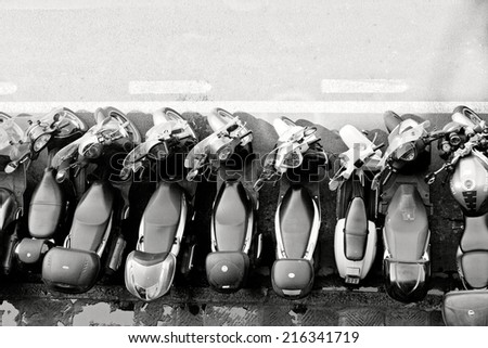 FLORENCE, ITALY - JUNE 11: Numerous motor scooters parking in Florence, Italy on June 11, 2014. Scooters are considered most popular transport in Italy. - stock photo