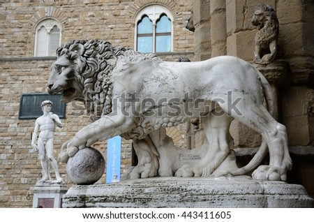 FLORENCE, ITALY - JUNE 9 2016: Sculpture of Medici lions and copy of Michelangelo's David statue is at Piazza della Signoria that is in front of the Palazzo Vecchio.
