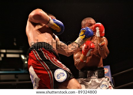 """FLORENCE, ITALY - NOV 4:  """"Daniele Petrucci"""" [Boxer-L] punches  """"Leonard Bundu"""" [Boxer-R] while fighting on ring at """"European Welter Boxing Title"""" in Florence, Italy on Nov 4, 2011. - stock photo"""