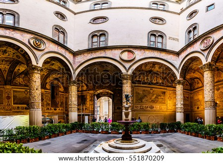 FLORENCE, Italy - NOVEMBER 22 2016: First courtyard with Putto with Dolphin by Verrocchio in middle, and frescoes of Austrian cities on wall by Vasari. Palazzo Vecchio is town hall of Florence, Italy.