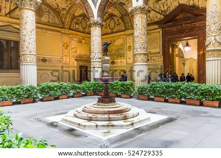 FLORENCE, ITALY - OCTOBER 26, 2016: View of the entrance courtyard of the Palazzo Vecchio. The colums are decorated with gilt stuccoes and the walls painted by Giorgio Vasari.