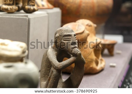 FLORENCE, ITALY - SEPTEMBER 20, 2015 : Close up detailed view of small basaltic olmec figurine exhibited in Florence Archeology Museum.