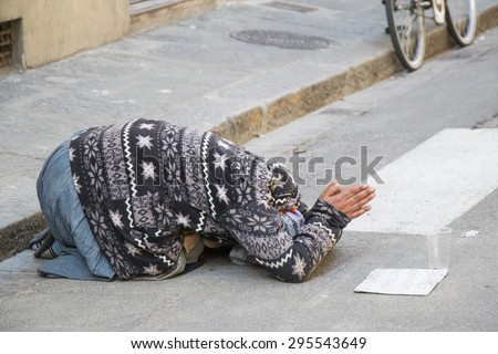 Florence - October 14: Unknown street beggar near Piazza del Duomo on Oct 26, 2014 in Florence, Italy. Due to the economic crisis in euro zone, job is hard to find. - stock photo