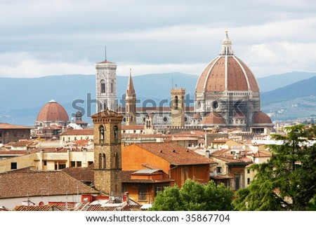 Florence seen from Michelangelo square: Palazzo Vecchio, the Duomo and Campanile Tower, beautiful sky, hills in the horizont. - stock photo