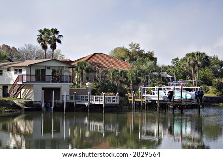 Florida homes along a waterway.  Boats and docks are in the backyard. - stock photo