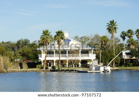 Florida Mansion Home on the water with palm trees - stock photo