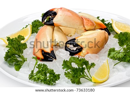 Florida stone crab claws on a bed of ice with lemon slices, and garnished with parsley. - stock photo