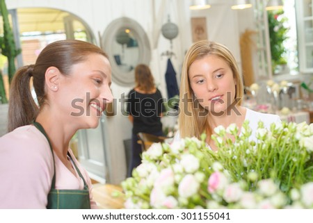 Florist advising a young customer what to buy - stock photo
