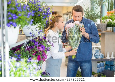 Florist and male customer smelling flower bouquet at store - stock photo