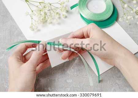Florist at work. How to make place card with handwritten name, decorated with flowers. - stock photo