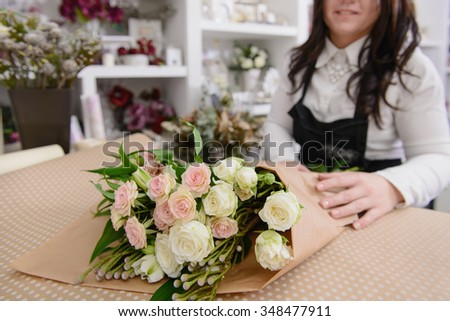 Florist at work: making bouquet of light roses on workspace, wrapping flowers
