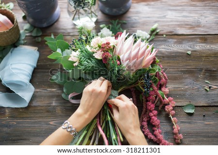 Florist at work: pretty young blond woman making fashion modern bouquet of different flowers - stock photo